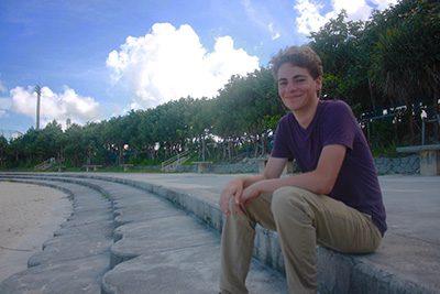 Henry sitting on beach.