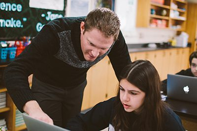 Science teacher helping student on computer