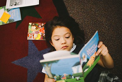 Lower School student reading a book