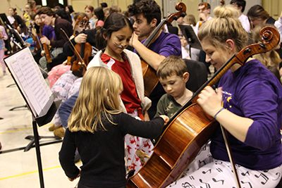 Elementary Students playing instrument with high school student