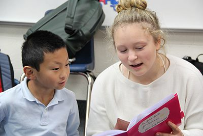 French III student reading to fourth grade French student