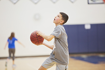 Student in gym playing basketball