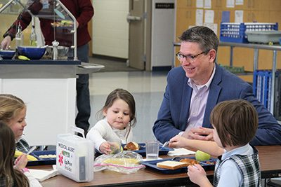 Dr. Hudson with PreK students at lunch