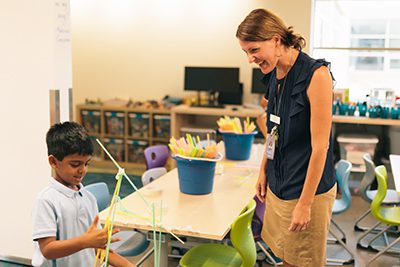 Teacher in Makerspace with young student