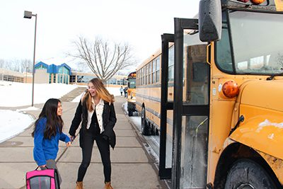 middle school students getting on the bus
