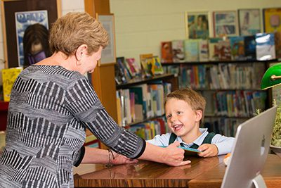 Librarian handing book to student