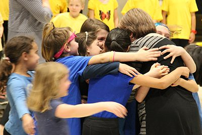 Ms. Rossbach's group hug at the lower school art and music show