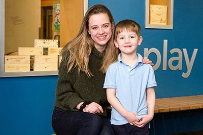 upper school student hugs lower school student outside of the makerspace