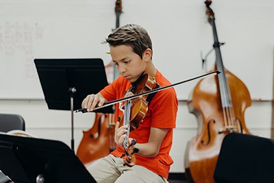 middle school student studies a sheet of music in orchestra