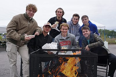 young alums around the bonfire at homecoming 2018
