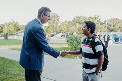 dr. Hudson shaking the hand of a middle school student on the first day of school