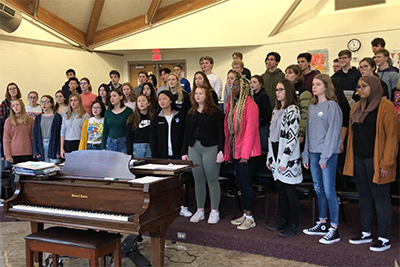 Upper school choir practicing the alma mater