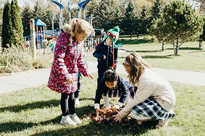 lower school students making a leaf pile