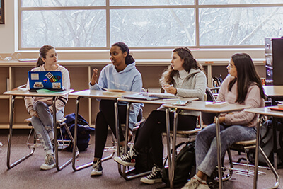 upper school students leading a discussion in class