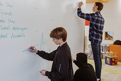 upper school students using makerspace whiteboard together