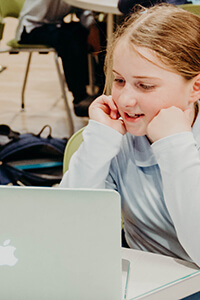 lower school student working on a laptop
