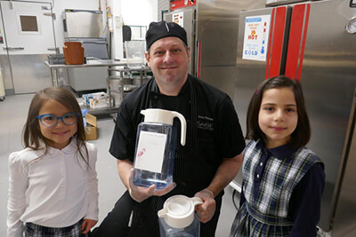Chef Doug with the lower school students and maple syrup