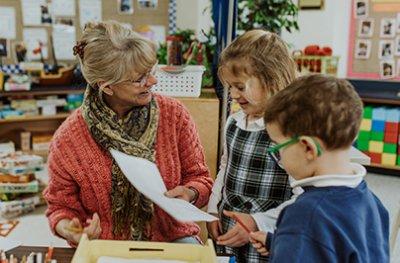 ms. Petersen working with two kindergarten students in class