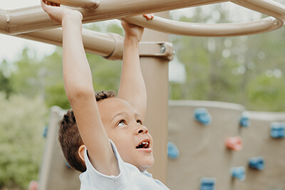 lower school student on the playground monkey bars