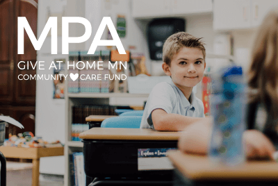 lower school student smiling at his desk
