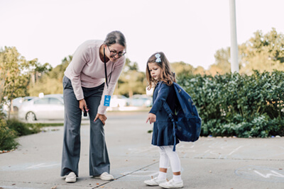 lower school student and parent arriving on campus