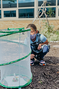 4th Grader Studying Butterflies in Courtyard