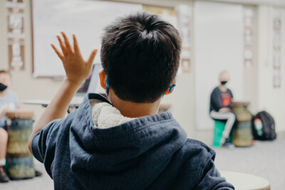 middle school student raising his hand