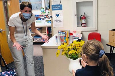 Kindergarten student delivering flowers to a teacher