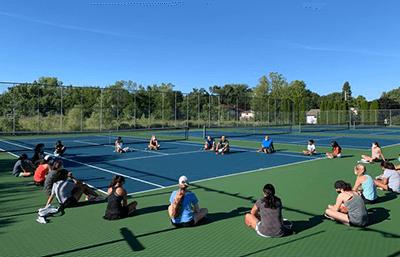 Girls Tennis Team Sitting on Courts