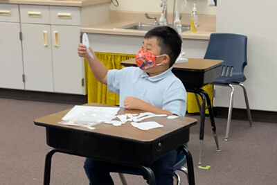 third grader working hands on in the classroom