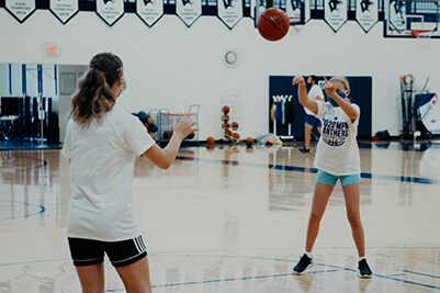 middle school girls passing a basketball