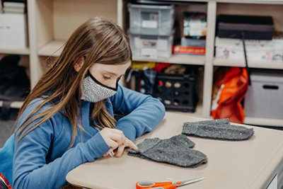 Fourth grader sewing annual mitten project
