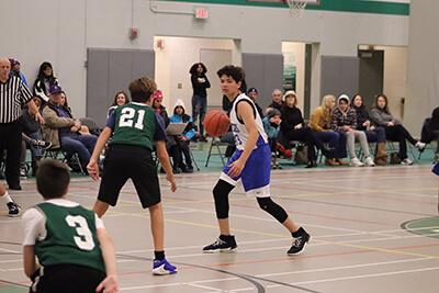 Micah dribbling the basketball vs. Hill Murray