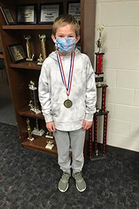Josh Murr in front of math trophy case wearing medal